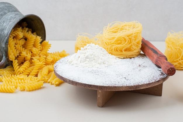 Rohe verschiedene makkaroni und mehl mit nudelholz