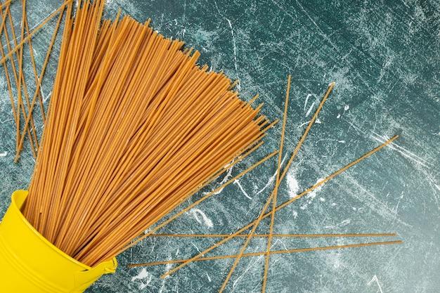 Rohe vollkornnudel-spaghetti in einem umgestürzten eimer auf dem blau.