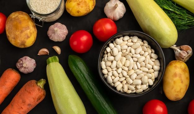 Rohe weiße bohne mit frischem gemüse auf schwarzem hintergrund. vegetarisches gesundes essen