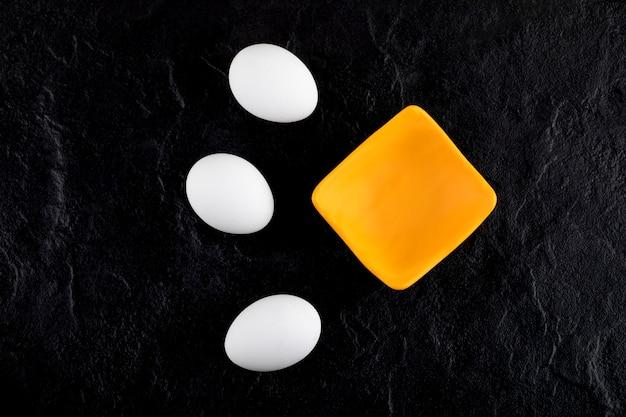 Rohe weiße eier und kleine schüssel auf schwarzer oberfläche.