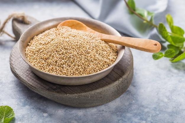Rohe weiße quinoa-samen auf teller mit holzlöffel