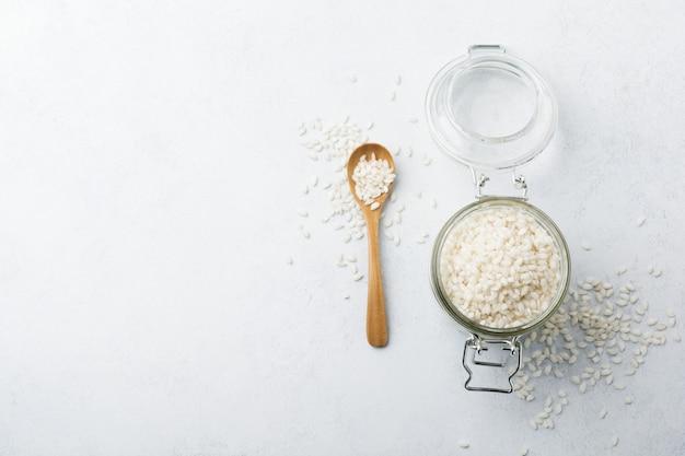 Rohe weiße reissorte arborio für italienische risottogerichte im glas auf weißem beton oder stein.