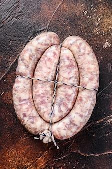 Rohe würste aus schweine- und rindfleisch auf dem holzbrett
