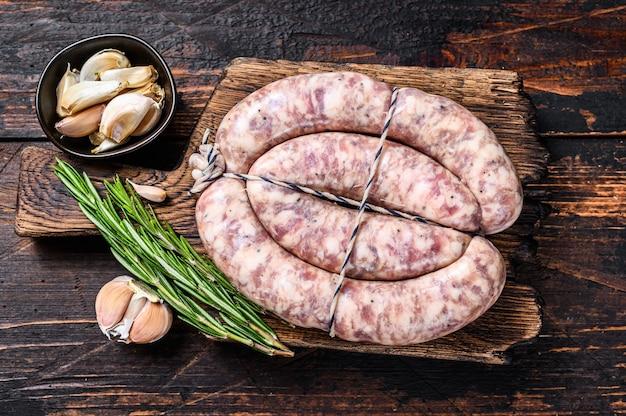 Rohe würste aus schweine- und rindfleisch auf dem holzschneidebrett