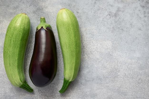 Rohe zucchini und lila auberginen. grauer hintergrund mit textfreiraum, bio-gemüse