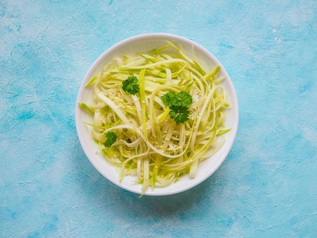 Rohe zucchininudeln auf blauem tisch, kopierraum