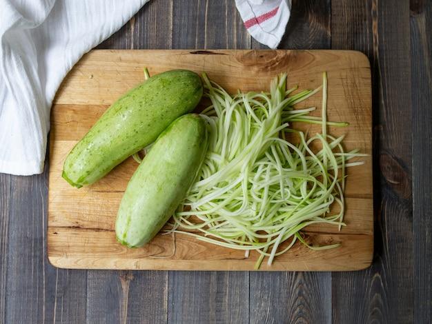 Rohe zucchininudeln auf dem holztisch, nah uo, draufsicht. vegan. gesundes essen.