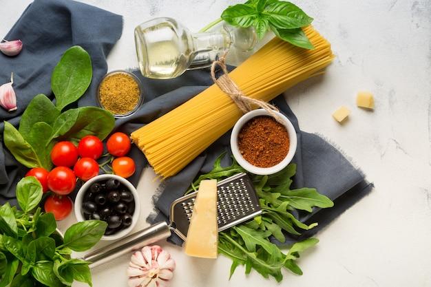 Rohe zutaten zum kochen von spaghetti auf weißem hintergrund. nudeln, tomaten, knoblauch, basilikum, parmesan und oliven