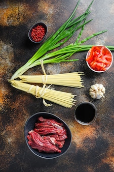 Rohe zutaten zum rühren braten nudeln mit gemüse und rindfleisch in schwarzer schüssel. auf altem rustikalem tisch.