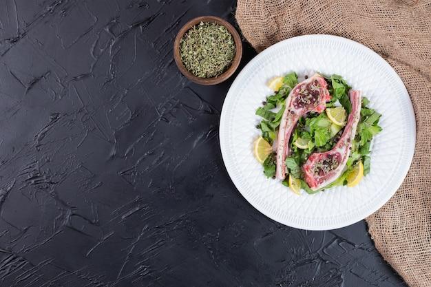 Rohe zwei rindfleischkoteletts auf weißem teller mit zitronenscheiben und grün.