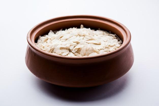 Roher, abgeflachter reis oder dicke oder dünne reisflocken für namkeen chivda snacks oder aloo poha für indisches frühstück, serviert in einer schüssel