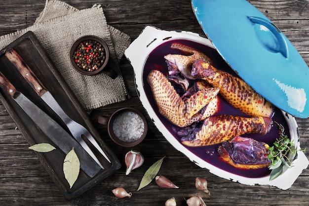 Roher bio-hahn in stücke geschnitten und in rotwein mit kräutern und gewürzen mariniert