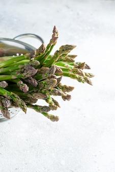 Roher bio-spargel in einem kochfertigen sieb
