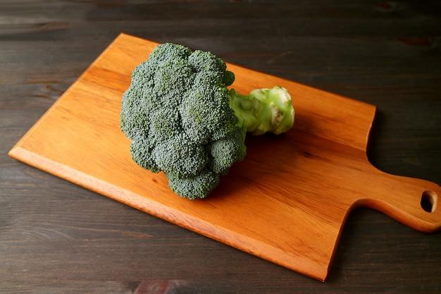 Roher brokkoli lokalisiert auf einem hölzernen schneidebrett