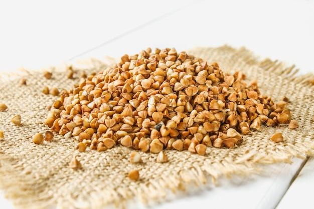 Roher buchweizen auf einem sack auf einem holztisch. gesunde ernährung
