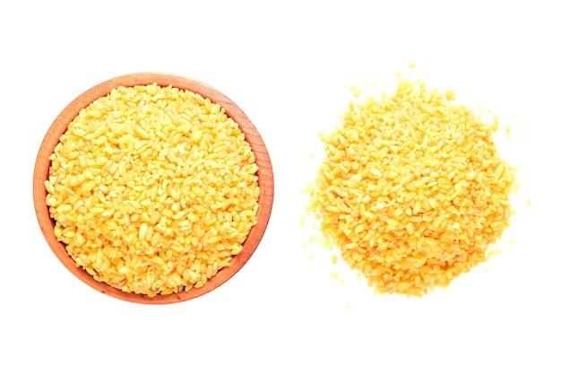 Roher bulgur in einer holzschale isoliert auf weißem hintergrund.trockenes bulgurkorn.gesunde ernährung.bio-produkt.draufsicht. platz kopieren.