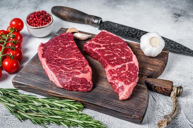 Roher denver schnitt schwarzes angus-bio-steak auf einem metzger-schneidebrett mit kräutern.