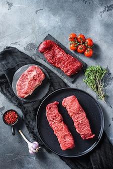 Roher denver, top blade, tri-tip-steak auf schwarzem teller und steinschiefer mit gewürzen