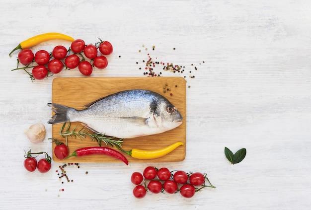 Roher dorada-fisch mit gemüse auf gesundem essen des hölzernen schneidebretts