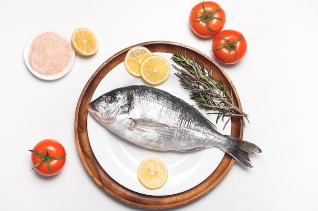 Roher dorada-fisch oder goldbrasse serviert auf weißem teller auf weißer oberfläche, flache lage, draufsicht