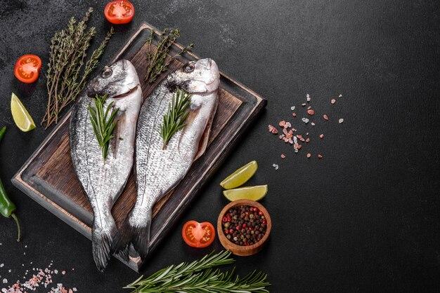 Roher dorado-fisch mit gewürzen, die auf schneidebrett kochen. dorado mit frischem fisch. dorado und zutaten zum kochen auf einem tisch
