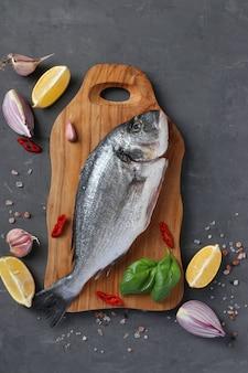 Roher dorado-fisch mit gewürzen, die auf schneidebrett kochen. sicht von oben. hochformat