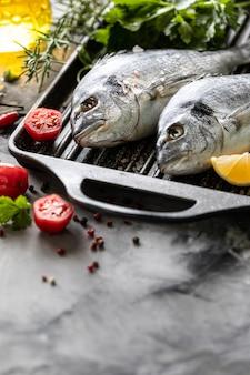 Roher dorado-fisch mit gewürzen, zitrone und petersilie in einer schwarzen grillpfanne auf weißem beton