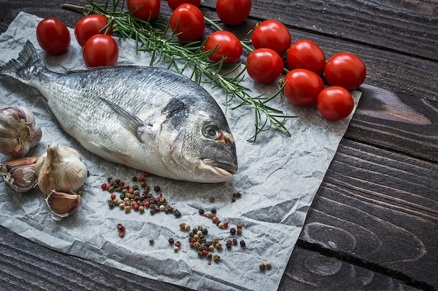 Roher dorado-fisch mit knoblauch und tomaten auf rustikalem tisch. seebrasse oder dorada fisch. draufsicht