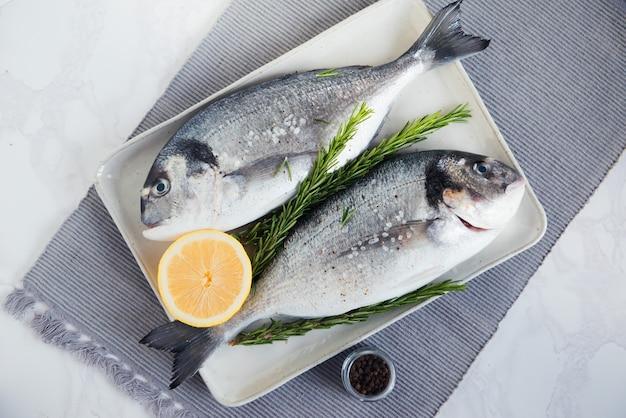Roher dorado-fisch mit zitrone und rosmarin, die zum kochen vorbereiten