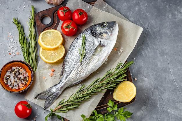 Roher dorado-fisch und gewürze zum kochen auf dem grau