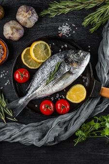 Roher dorado-fisch und gewürze zum kochen in einer pfanne auf schwarz