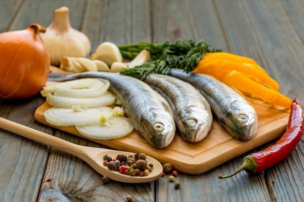 Roher fisch auf küchentisch mit zutaten zum kochen