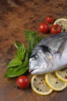 Roher fisch dorado mit basilikum, zitronenscheiben, kirschtomaten auf dem tisch