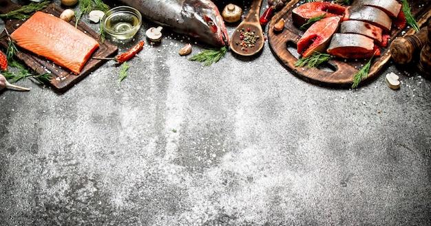 Roher fisch. ein stück frischer lachs mit gewürzen auf altem schneidebrett auf rustikalem tisch.