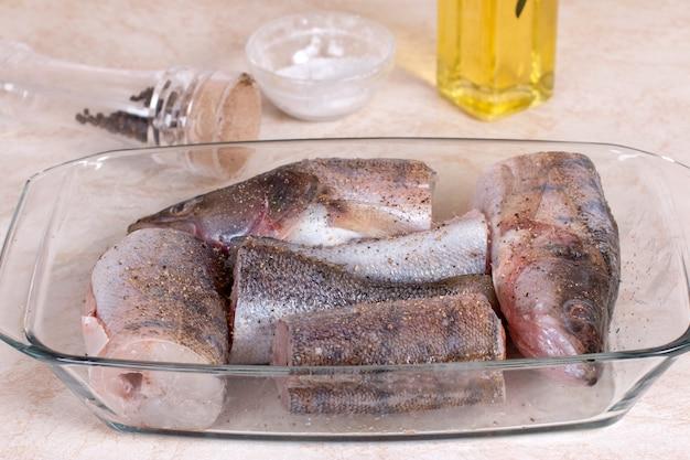 Roher fisch in einer glasbackform auf dem küchentisch