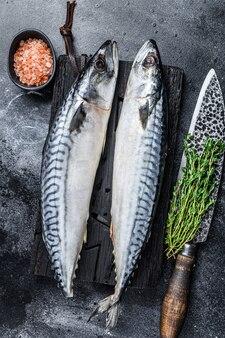 Roher fisch makrele auf einem holzbrett.