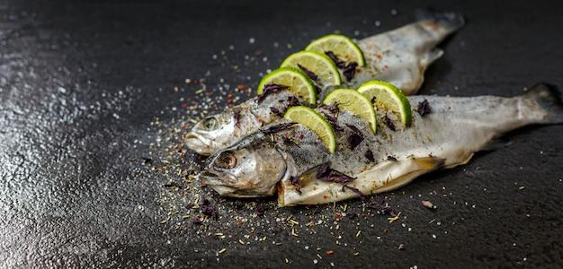 Roher fisch mit aromatischen kräutern, gewürzen, salz- und limettenscheiben. rohe flussforelle auf schwarzem steinbehälter.