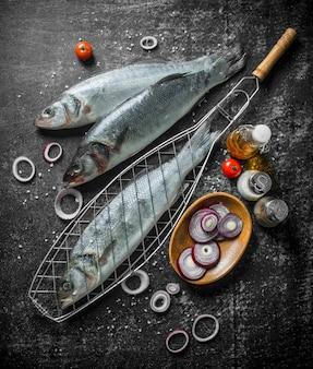Roher fisch mit gewürzen, tomaten und zwiebelringen auf rustikalem tisch.