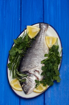 Roher fisch mit kräutern und zitrone auf teller auf holzoberfläche