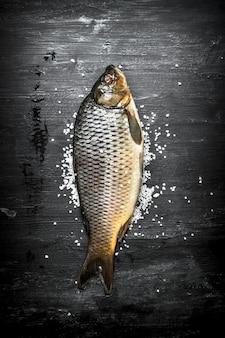 Roher fisch mit salz auf schwarzem holztisch.