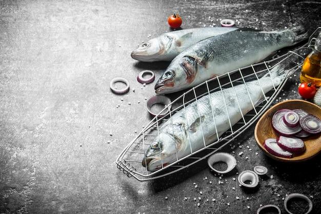 Roher fisch seebarsch auf dem grill mit gehackten zwiebeln auf dunklem rustikalem tisch