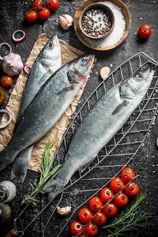Roher fisch seebarsch auf gitter mit tomaten und gewürzen auf dunklem rustikalem tisch
