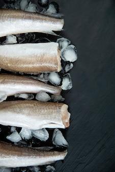 Roher fisch seehecht. fünf rohe fischfilets auf eis auf dunklem,