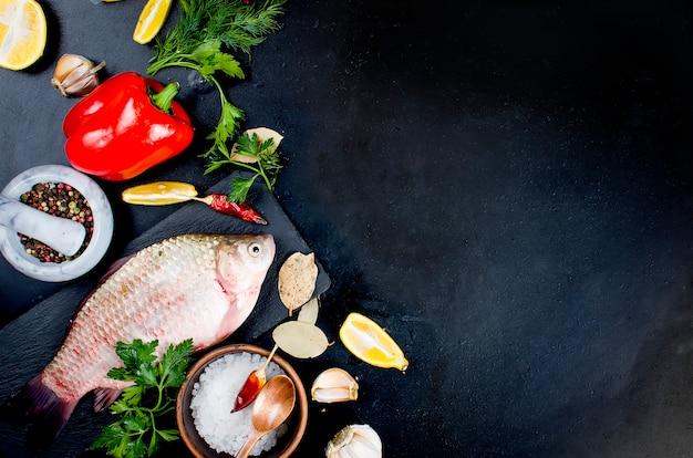 Roher fisch und zutaten zum kochen auf dunkel.