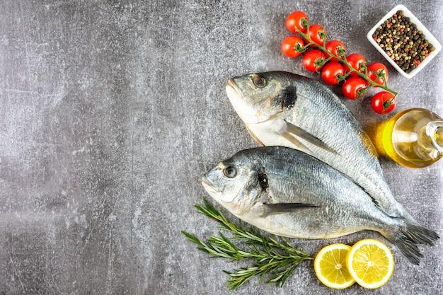 Roher fischdorado auf grauem betonhintergrund mit gewürzen, tomate, rosmarin, olivenöl und zitrone. ansicht von oben, flach mit kopienraum für text