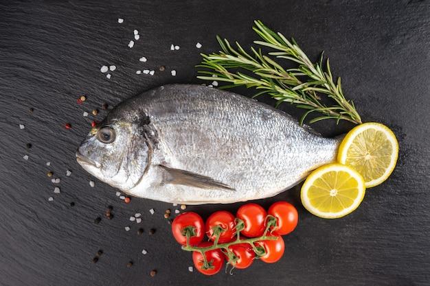 Roher fischdorado auf schwarzem schieferhintergrund mit gewürzen, tomate, rosmarin, olivenöl und zitrone. ansicht von oben, flach mit kopienraum für text