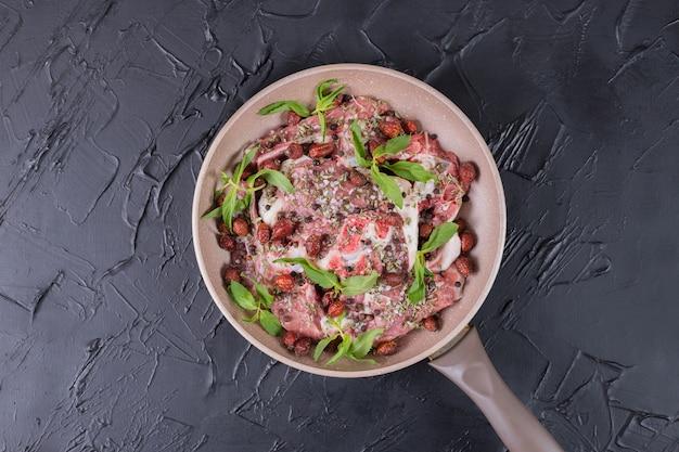 Roher fleischsalat mit frischer minze in einer pfanne auf dunkler oberfläche.