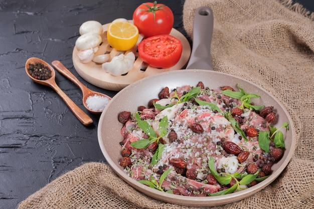 Roher fleischsalat mit frischer minze in pfanne und teller mit frischem gemüse.