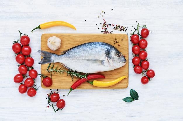 Roher frischer dorado-fisch mit gemüse und gewürzen. gesundes lebensmittelkonzept. draufsicht, kopierraum. mediterranes meeresfrüchte-konzept.