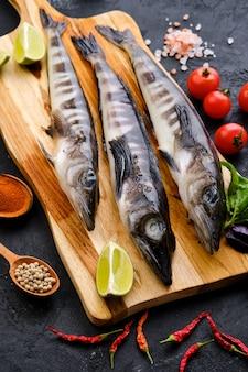 Roher frischer eisfisch auf hölzernem schneidebrett mit gewürzen und kräutern
